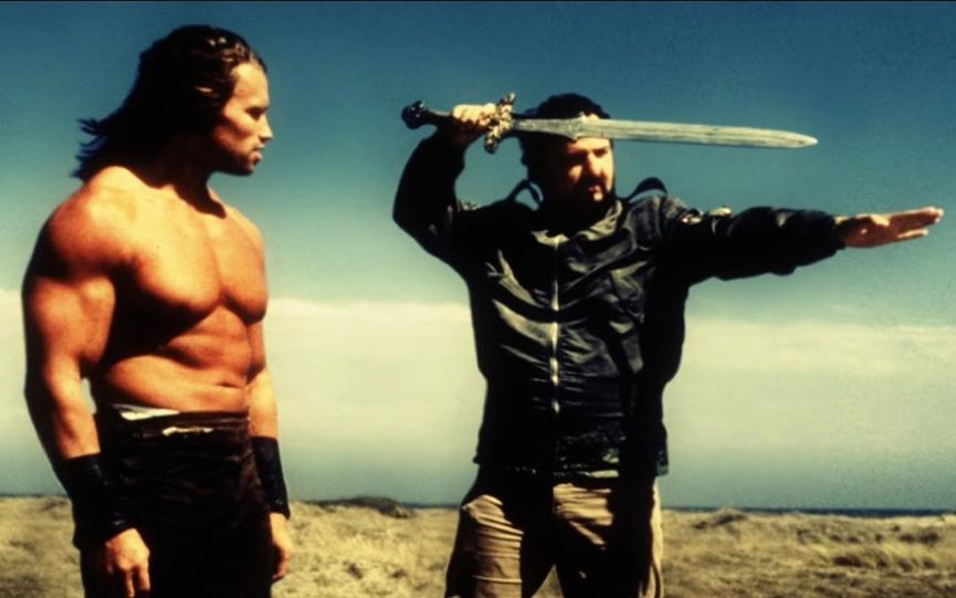 《 王者之劍 》中,導演約翰米遼士 (右) 正指導 阿諾 (左) 舞劍。