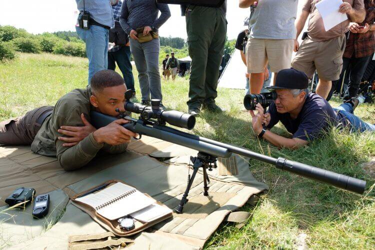 李安執導《雙子殺手》電影拍攝場邊花絮照片,威爾史密斯正看著狙擊槍上的瞄準鏡。