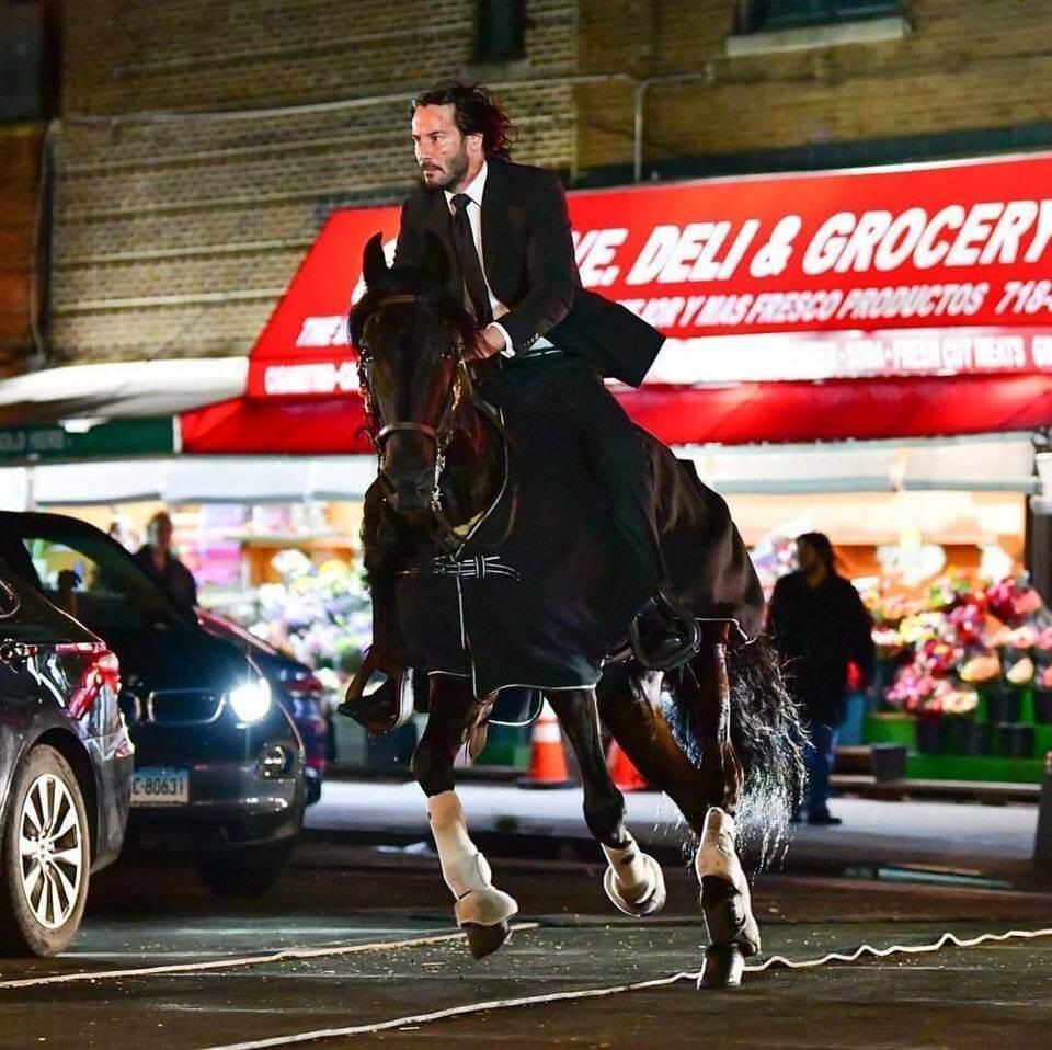 《捍衛任務 3》拍攝現場的場邊花絮照,圖為騎馬躲避追兵的約翰維克(基努李維 飾)。
