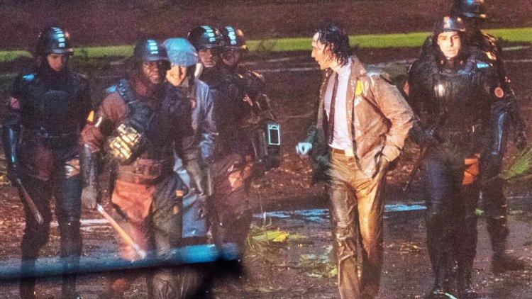 《洛基》影集流出片場照,湯姆希德斯頓看起來像遭到神秘雨衣男子帶領的警隊逮捕。